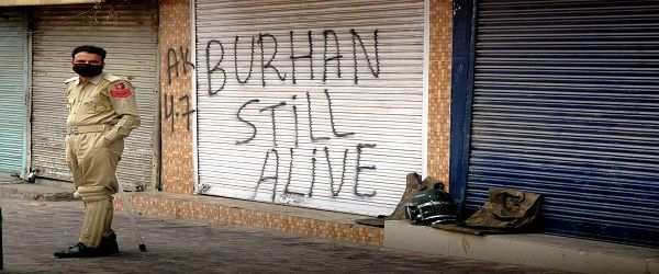 "A security personnel stands in front of a closed shops at Amirakadal ascribed by a slongan ""Burhan Still alive"" a Hizbul Mujahideen Commander who was gunned down in an encounter in south Kashmir on July 8 led authorities to clamp Curfew, restrictions in Shehar-e-Khas, down town and parts of Srinagar city following strike call by separatist organisations on the fourth consecutive day"