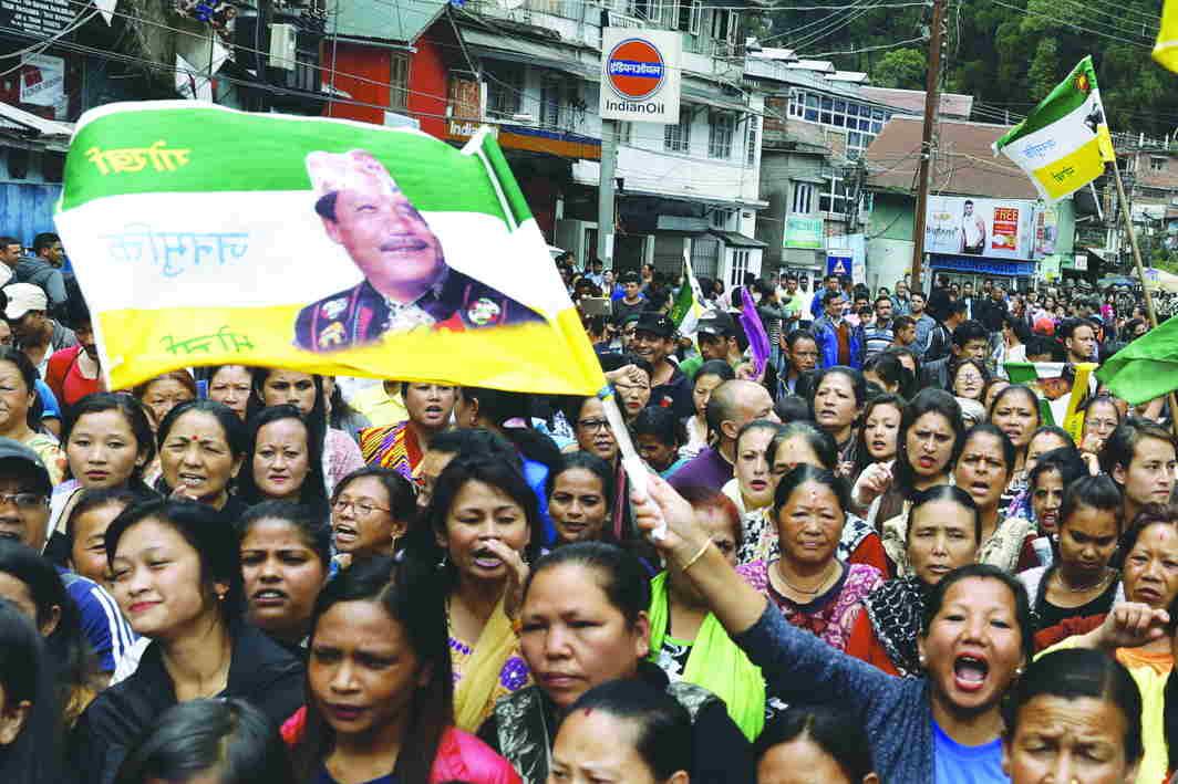 Crowds carrying Gorkha Janamukti Morcha flags with Bimal Gurung's image on them