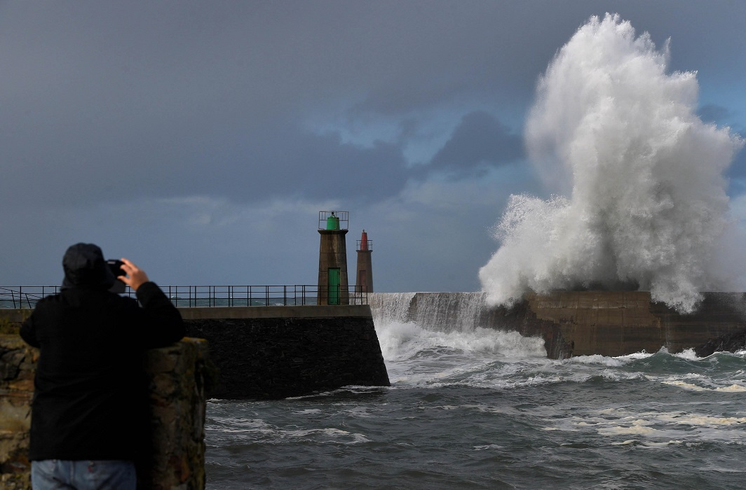 THE BIG PICTURE: A man takes a picture of the waves as they crash against a lighthouse in the northern Spanish village of Viavelez, Spain, January 13, Reuters/UNI