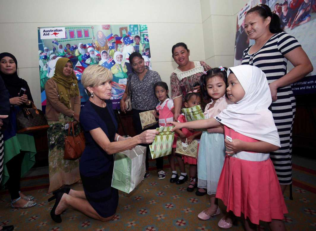 LOVE, OFFICIALLY: Australian Foreign Affairs Minister Julie Bishop hands over a gift to a student from the Autonomous Region of Muslim Mindanao (ARMM) during a visit in Davao city, southern Philippines, Reuters/UNI
