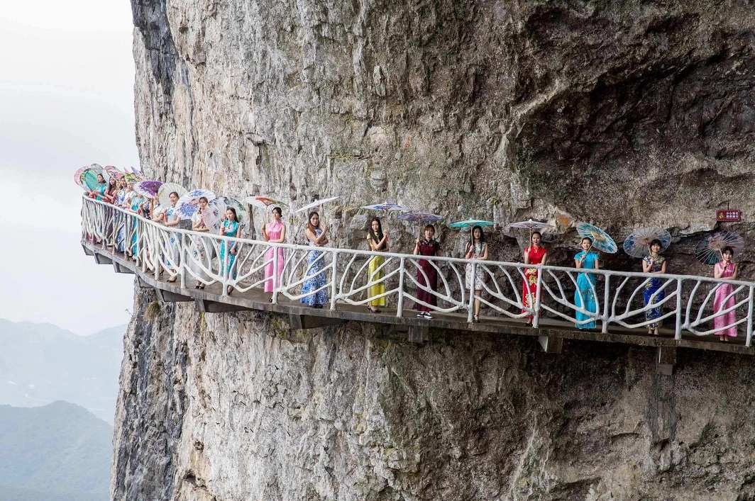 MAKING A STAND: Women wearing cheongsam, a one-piece dress, pose for pictures on a walkway along a cliff during an event in Chongqing Municipality, China March 26, 2017, Reuters/UNI
