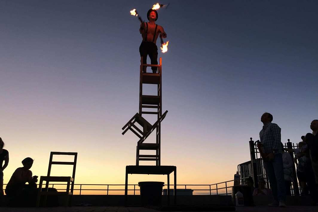 AMAZING AGILITY: A performer stands on a stack of chairs and juggles fire torches at sunset in Key West, Florida, Reuters/UNI