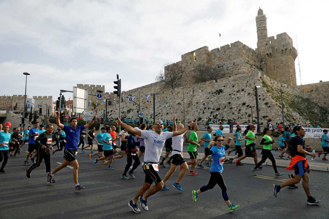 TO GO FASTER AND FARTHER: Athletes run outside Jerusalem's Old City during the seventh International Jerusalem Marathon, Reuters/UNI