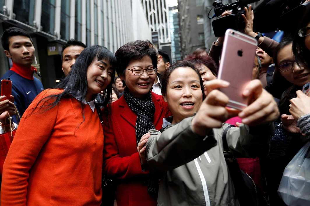 HER MOMENT IN THE SUN: People take selfies with Carrie Lam, chief executive-elect, a day after she was elected in Hong Kong, Reuters/UNI