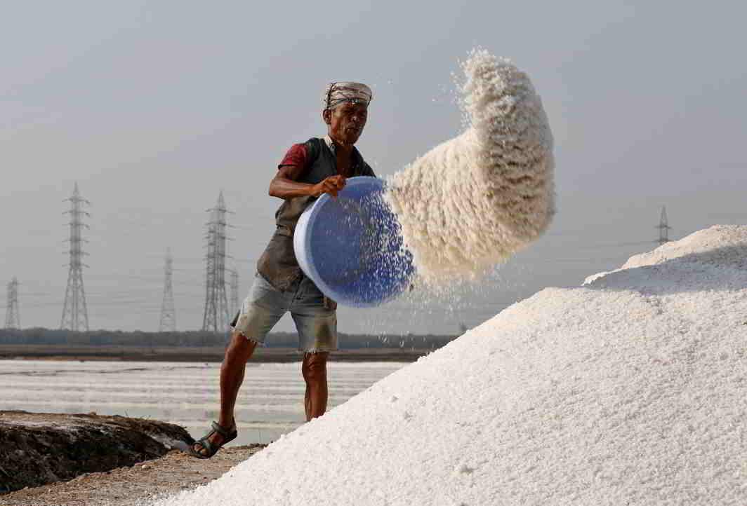ALL IN A DAY'S WORK: A labourer empties a salt basket in a salt pan in Mumbai, Reuters/UNI