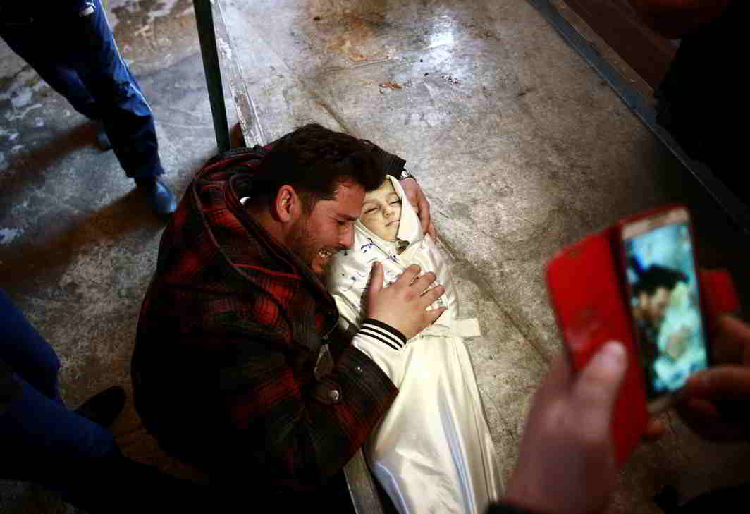 UNSPEAKABLE LOSS: A man grieves for his daughter following an airstrike on the rebel-held besieged city of Douma, in the eastern Damascus suburb of Ghouta, Syria, Reuters/UNI