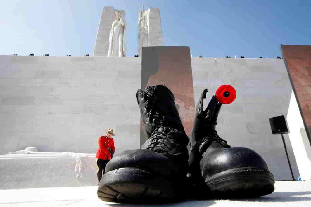 WWI MEMORIES: Military boots symbolising dead soldiers are seen as a Canadian police mounted officer stands guard before the ceremony to commemorate the 100th anniversary of the battle of Vimy Ridge, at Canadian National Memorial in Vimy, France, Reuters/UNI
