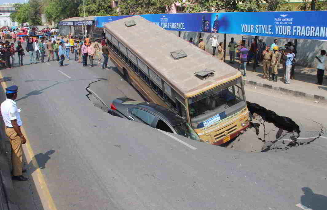 CLOSE SHAVE: A metro transport corporation bus and a car, following a road cave-in in Chennai, UNI