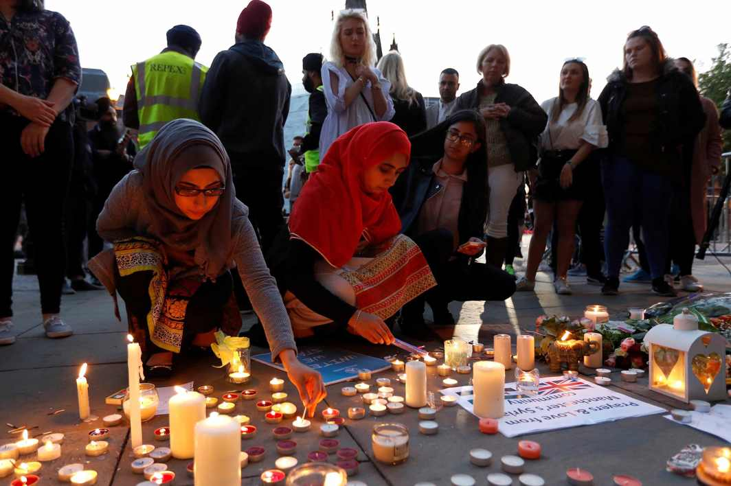 REMEMBER THE CHILDREN: Women light candles following a vigil in central Manchester, Reuters/UNI