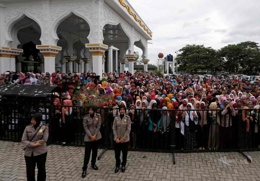 TRAGIC SPECTACLE: Indonesian policewomen guard people who watch a man publicly caned for having gay sex, in front of Syuhada mosque in Banda Aceh, Aceh province, Indonesia, Reuters/UNI