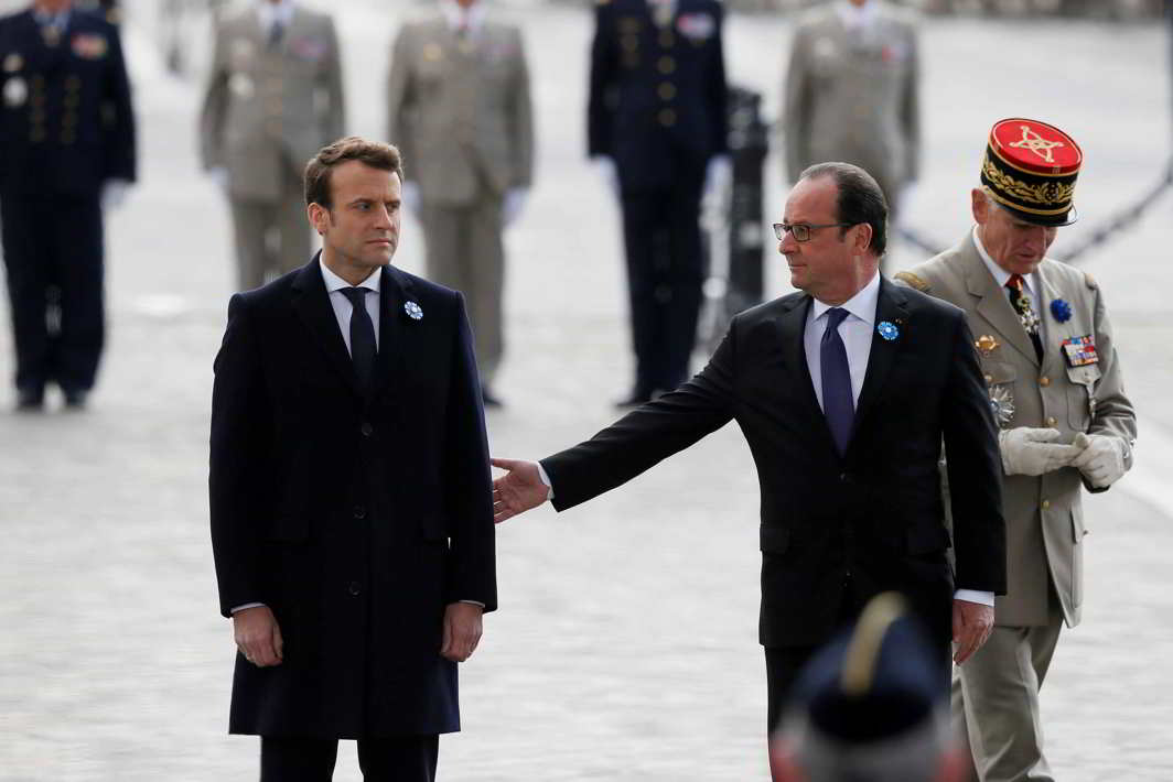 OLD MEETS NEW: Outgoing French President Francois Hollande (R) reaches out to President-elect Emmanuel Macron, as they attend a ceremony to mark the end of World War II at the Tomb of the Unknown Soldier at the Arc de Triomphe in Paris, Reuters/UNI