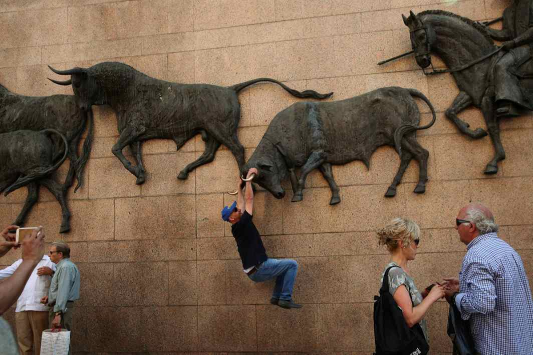 SHADOWFIGHTING: A man has his photo taken hanging from a bull sculpture outside Las Ventas bullring during San Isidro's bullfighting fair in Madrid, Reuters/UNI