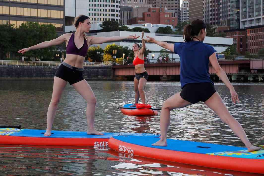 """PERFECT FLOW: People take part in a """"Sup Yo, Boston"""" stand-up paddle board yoga class on Fort Point Channel on International Yoga Day in Boston, Massachusetts, US, Reuters/UNI"""