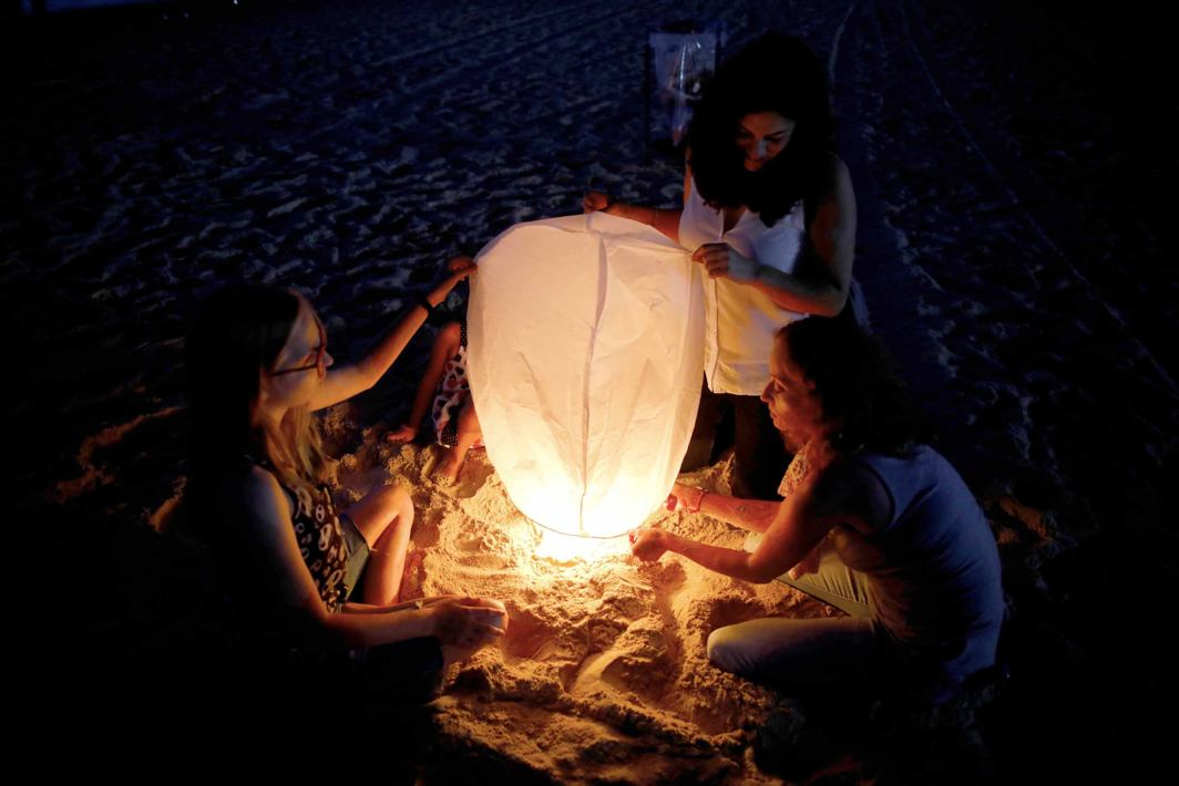 LET THERE BE LIGHT: Israeli peace activists prepare a sky lantern before releasing it, hoping to illuminate the sky in Gaza, as they protest Israel's reduction of power supply to Gaza at a beach in Ashkelon, southern Israel, Reuters/UNI