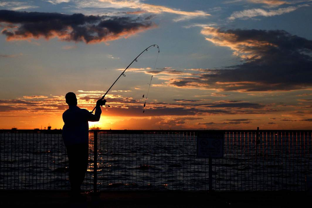 EVENING: A fisherman casts his line during sunset in the Brooklyn borough of New York City, US, Reuters/UNI