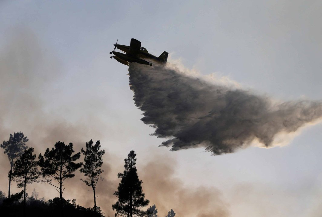 INFERNO UNDER: A firefighting plane dumps water on a forest fire in Mendeira, Portugal, Reuters/UNI
