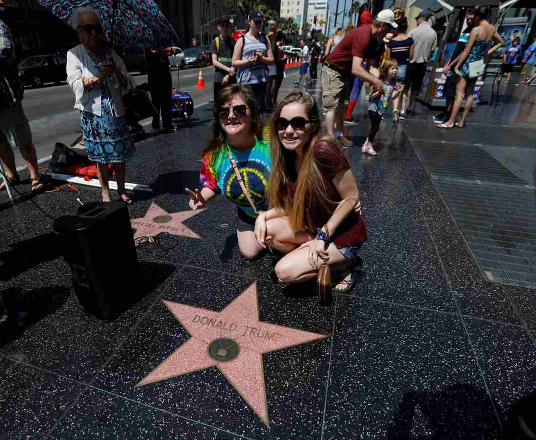 GLAMOUR AND PROTEST: People pose by the star of Donald Trump on the Hollywood Walk of Fame during a news conference to announce nationwide protests in Los Angeles, California, US, Reuters/UNI
