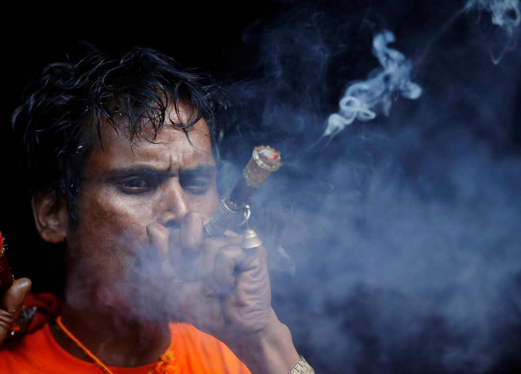 "PASHUPATINATH CALLS: A devotee smokes marijuana as he takes part in the ""Bol Bom"" (or Say Shiva) pilgrimage in Kathmandu, Nepal, Reuters/UNI"