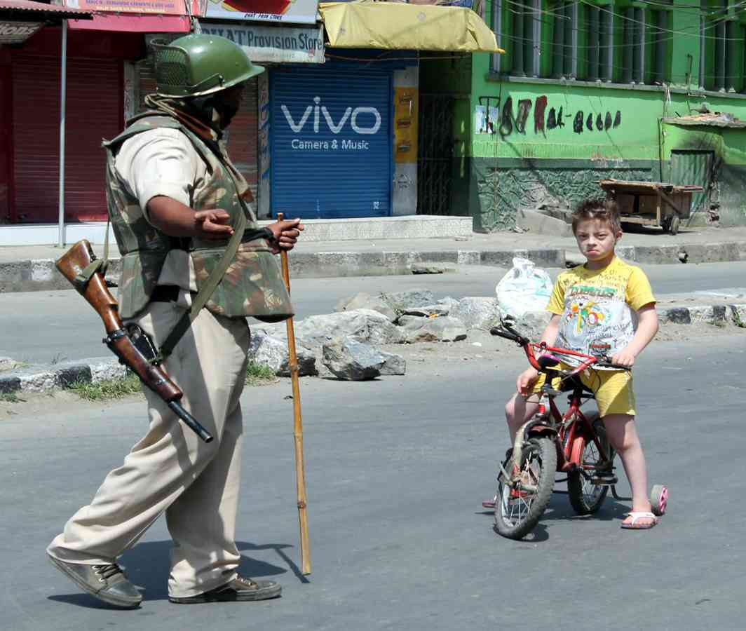 NEVER TOO YOUNG: A security personnel stops a young boy on his bicycle playing on a deserted road in Srinagar, UNI