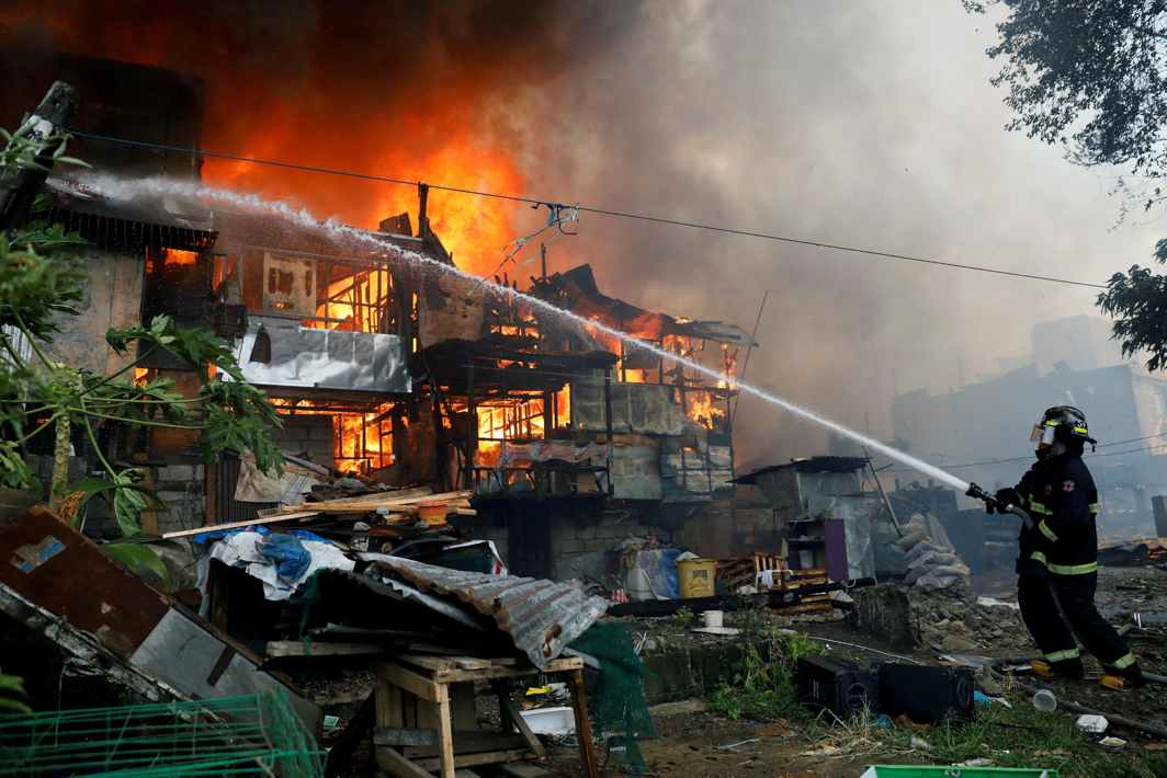 FULL FORCE: A firefighter aims water on shanties engulfed in flames during a fire in a residential area in Quezon City, Metro Manila, Philippines, Reuters/UNI