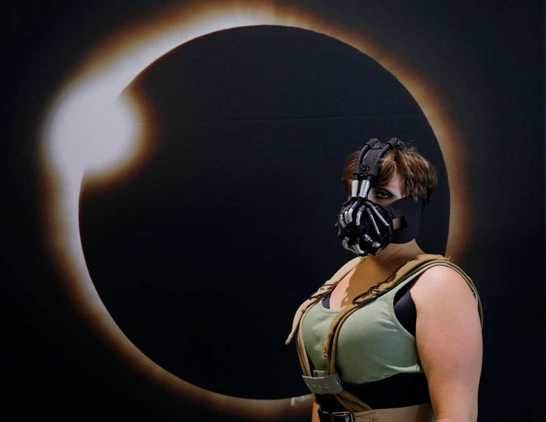 WHEN THE SUN DISAPPEARED: A woman poses for a photograph in front of an image of a solar eclipse at the Eclipse Comic-Con at Southern Illinois University in Carbondale, Illinois, US, Reuters/UNI