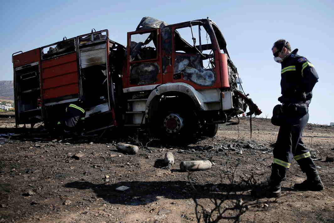 TO NO AVAIL: A firefighter drops water on a gutted fire truck as another stands by following a wildfire in the area of Kalyvia, near Athens, Reuters/UNI