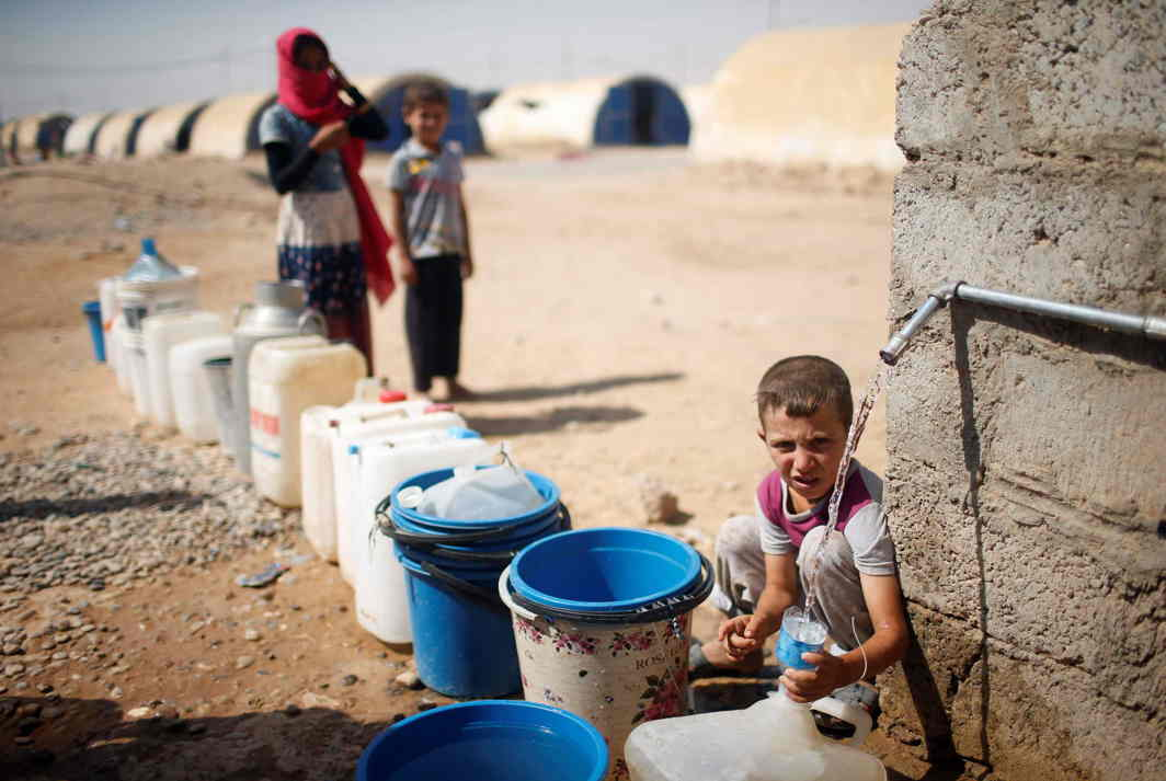 HOW FAIR IS LIFE? A displaced Iraqi boy fills a bottle with water in Jada camp south of Mosul, Iraq, Reuters/UNI