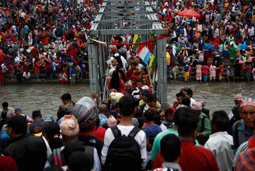 HONOURING THE FATHER: Devotees cross a bridge over the Bagmati to perform religious rituals on the banks of the river during Kuse Aunse (Fathers Remembrance Day) at Gokarna Temple in Kathmandu, Nepal, Reuters/UNI