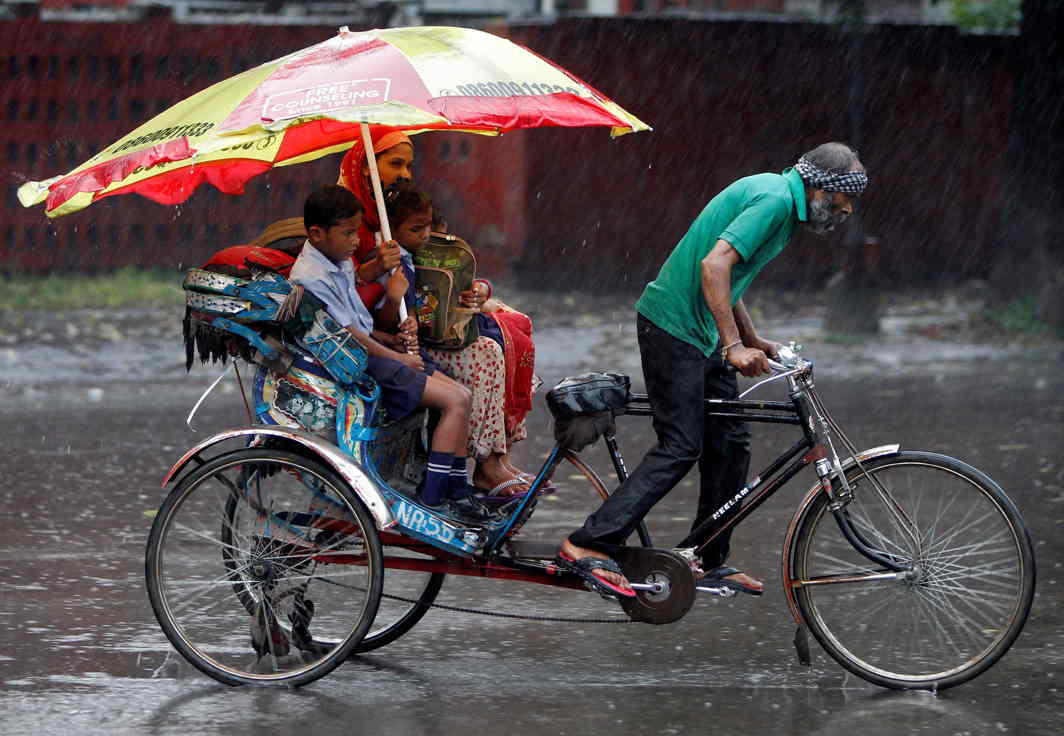 PORTRAIT OF DAILY LIFE: A woman and her children ride a rickshaw during heavy rains in Chandigarh, Reuters/UNI