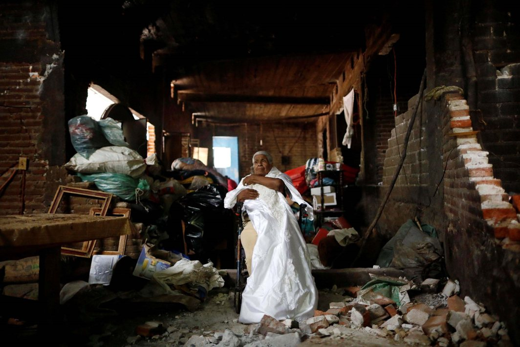 FIRST ON HER MIND: Justina Escamilla, 88, poses for a photo as she holds her wedding dress inside her destroyed house after an earthquake in San Juan Pilcaya, at the epicenter zone, Mexico. Justina returned to the interior of her house to retrieve her dress during the earthquake, Reuters/UNI