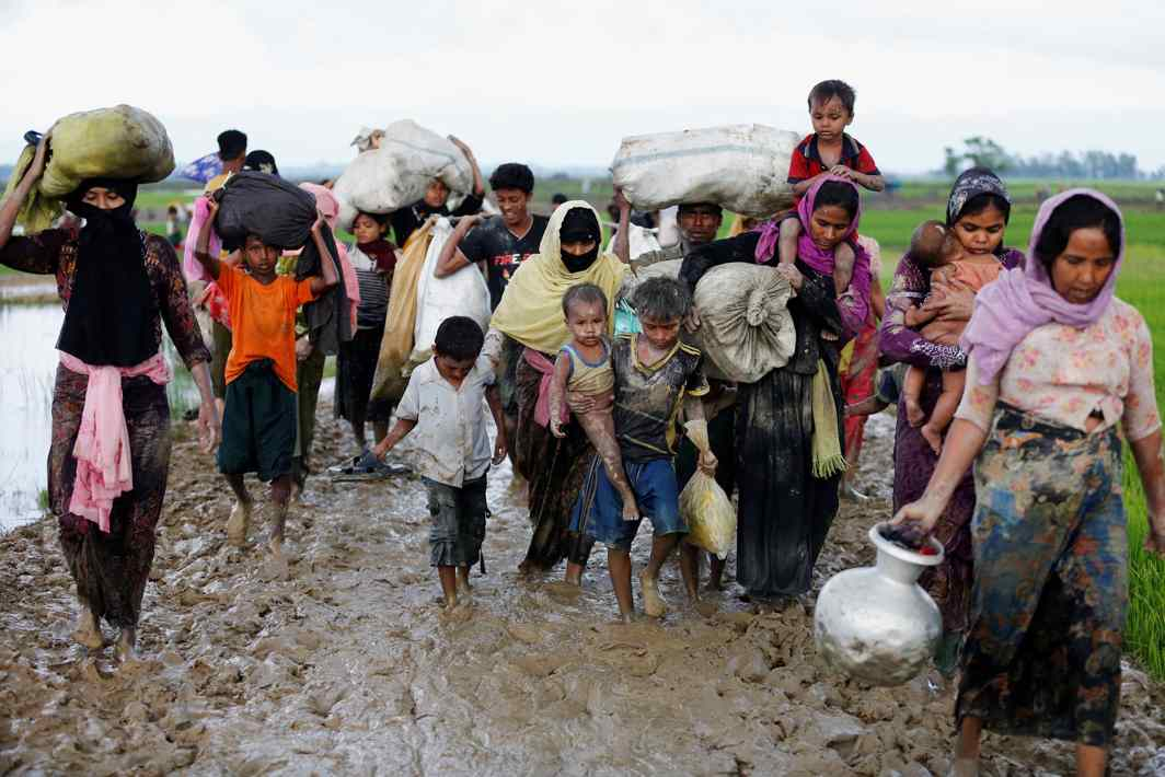 WALKING WITH THE LORD: A group of Rohingya refugees walk on the muddy road after travelling over the Bangladesh-Myanmar border in Teknaf, Bangladesh, Reuters/UNI