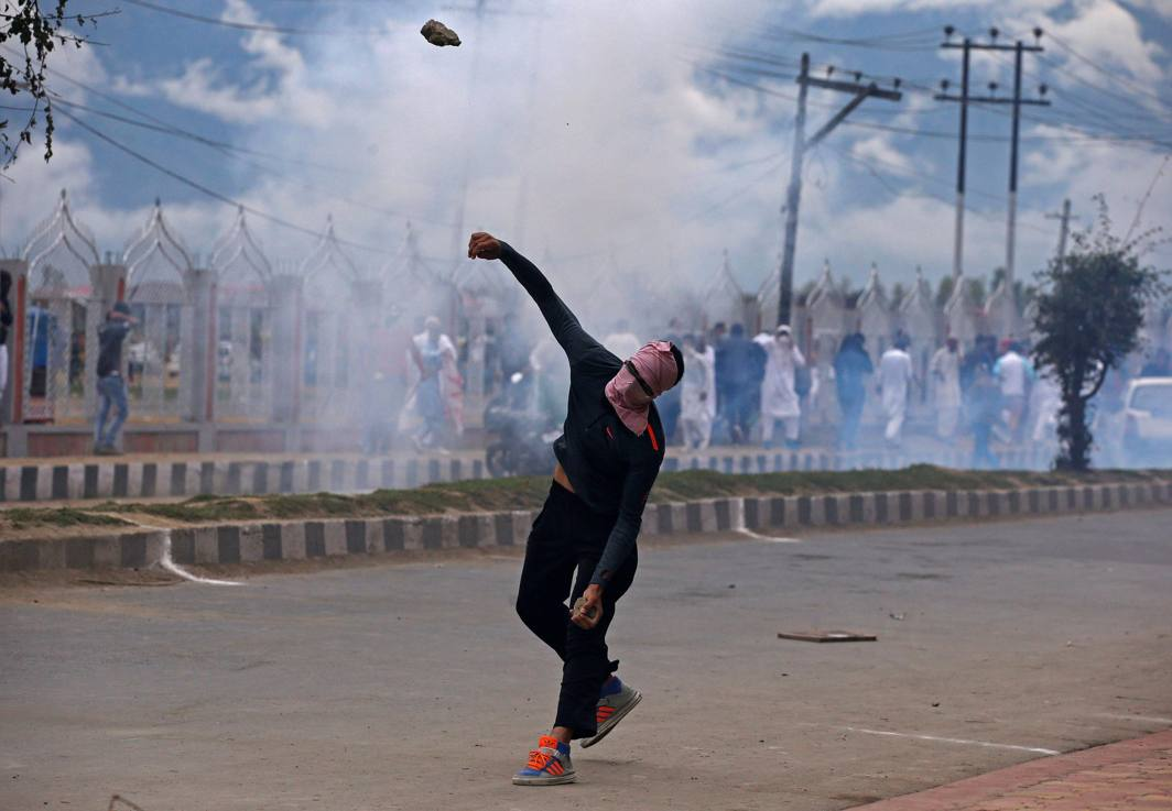 VIOLENT EID: A demonstrator hurls a stone amid smoke from a tear gas shell fired by police during clashes after the Eid al-Adha prayers in Srinagar, Reuters/UNI