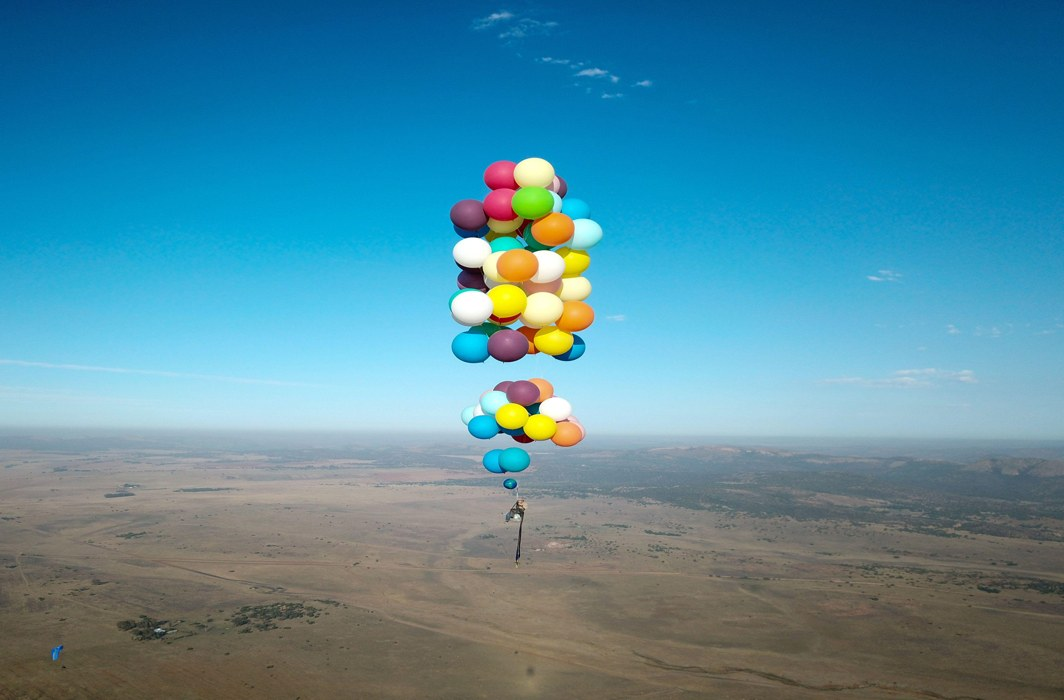 PRETTILY RISKING: Tom Morgan, from Bristol-based company The Adventurists, flies in a chair with large party balloons tied to it near Johannesburg, South Africa, The Adventurists and Richard Brandon Cox/Reuters/UNI