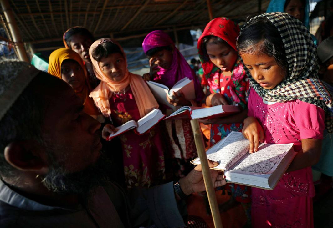 SOLACE IN ATAVISM: A Rohingya refugee girl reads the Quran to her teacher during a Quran reading lesson at a mosque in Palong Khali refugee camp near Cox's Bazar, Bangladesh, Reuters/UNI