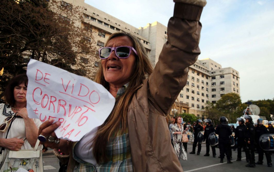 "CRY FOR JUSTICE: A woman holds a sign against former Planning Minister Julio De Vido outside the federal justice building where De Vido turned himself in to authorities, in Buenos Aires, Argentina. The sign reads ""Corrupt De Vido, go away"", Reuters/UNI"