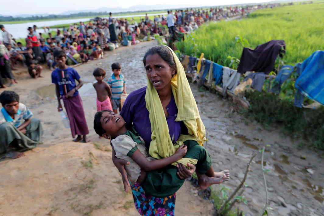 IN DESPAIR: A Rohingya refugee woman who crossed the border from Myanmar a day before carries her daughter and searches for help as they wait to receive permission from the Bangladeshi army to continue their way to the refugee camps, in Palang Khali, Bangladesh, Reuters/UNI