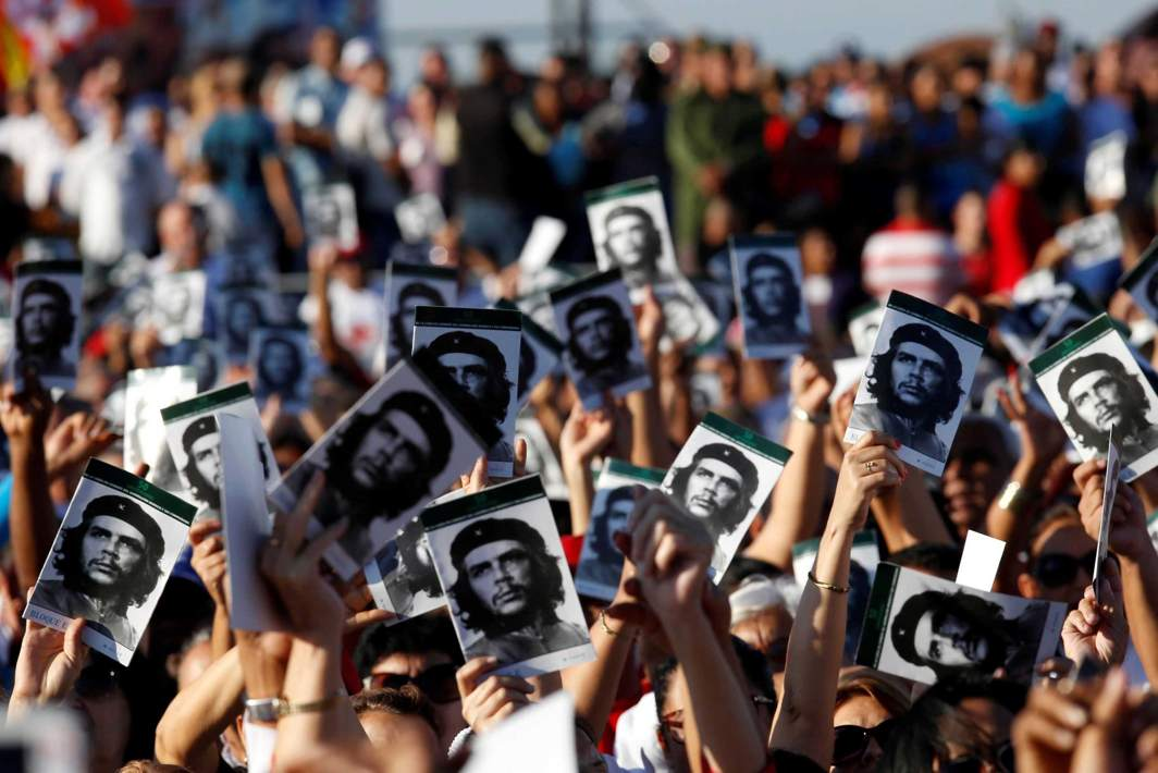 """REMEMBER: People hold images of late Cuban revolutionary hero Ernesto """"Che"""" Guevara during a ceremony commemorating the 50th anniversary of his death, Santa Clara, Cuba, Reuters/UNI"""