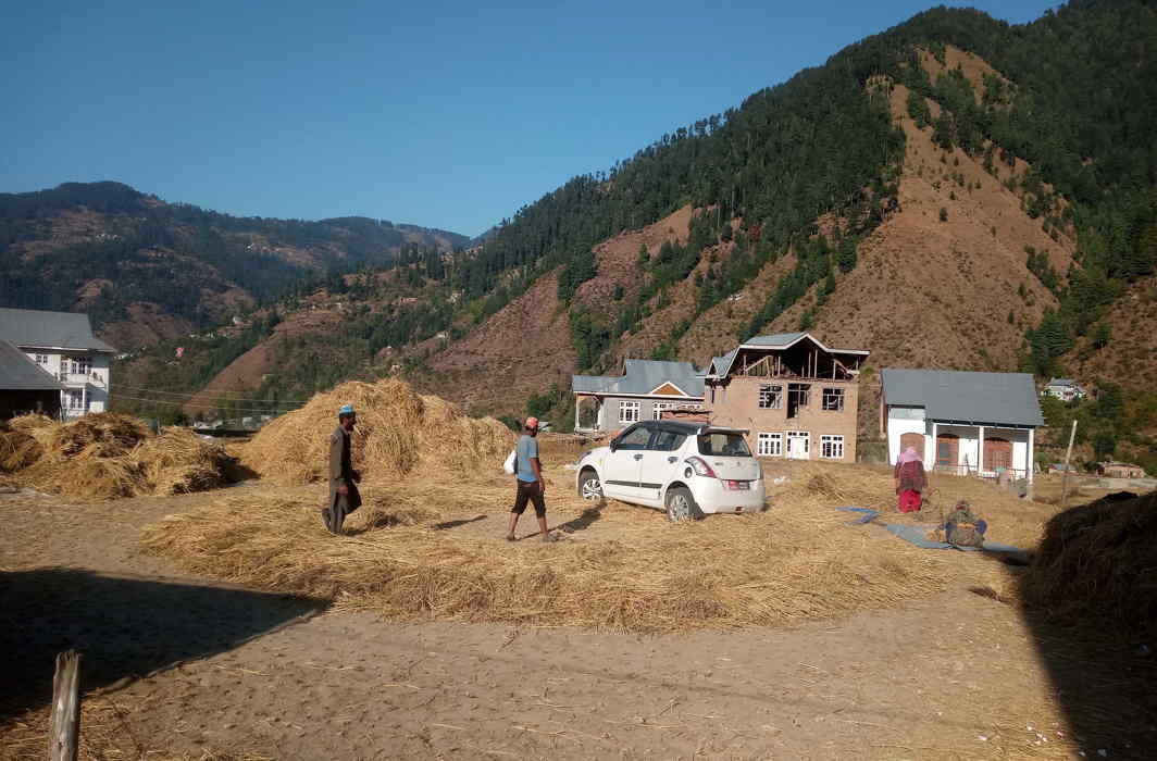 PUT TO WORK: Farmers use a Maruti Swift for threshing paddy at Sungle village in Bhaderwah valley in Jammu and Kashmir, UNI