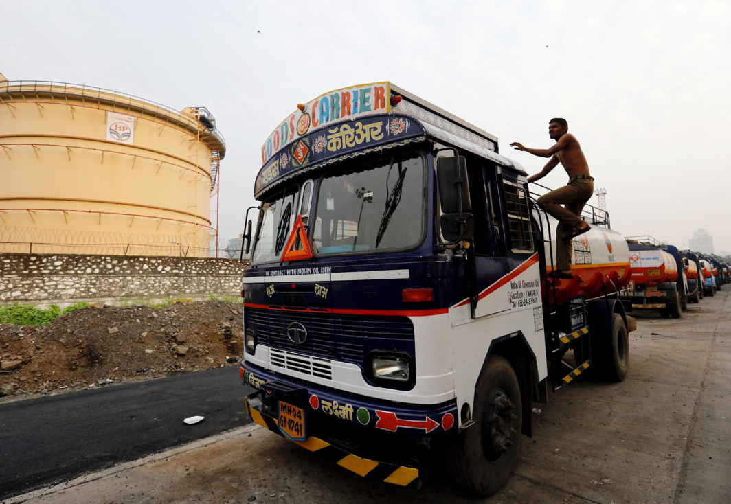 HERE WE GO: A man climbs an oil tanker parked outside a fuel depot in Mumbai, India, Reuters/UNI