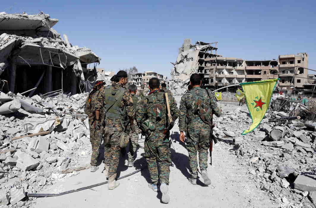 IRREPARABLE LOSS: Fighters of Syrian Democratic Forces walk past ruins of destroyed buildings near National Hospital after Raqqa was liberated from Islamic State militants, in Raqqa, Syria, Reuters/UNI