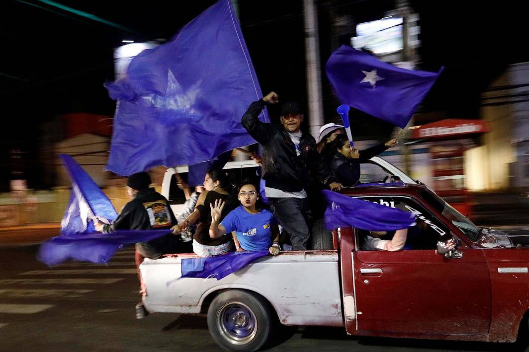 NATIONAL COLOURS: Supporters of the president and National Party presidential candidate Juan Orlando Hernandez take part in a vehicle caravan rally as they wait for official presidential election results in Tegucigalpa, Honduras, Reuters/UNI