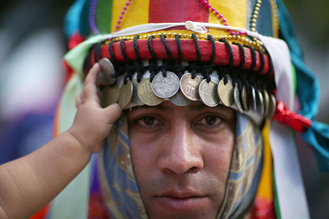 DASHING HERO: A traditional dancer uses coins as ornaments on his costume in San Salvador, El Salvador, Reuters/UNI