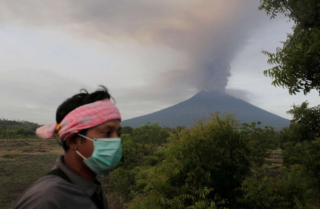ASH IN YOUR BREATH: A villager walks as Mount Agung volcano erupts in the background in Kubu, Karangasem, Bali, Indonesia, Reuters/UNI