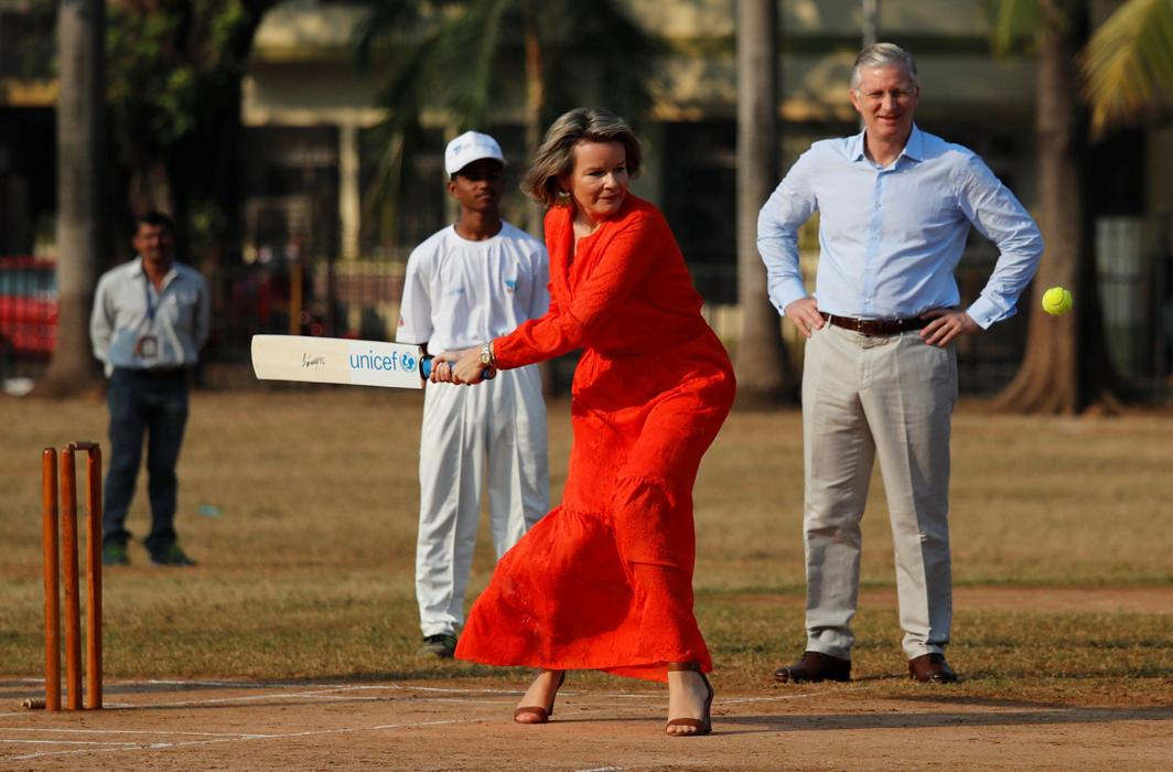 QUEEN'S GAME: Belgium's King Philippe looks on as Queen Mathilde hits a ball as they play cricket with children at a ground in Mumbai, India, Reuters/UNI