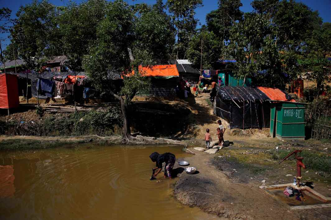 LIFE GOES ON: A Rohingya refugee washes her clothes in a pond at Kutupalong refugee camp near Cox's Bazar, Bangladesh, Reuters/UNI