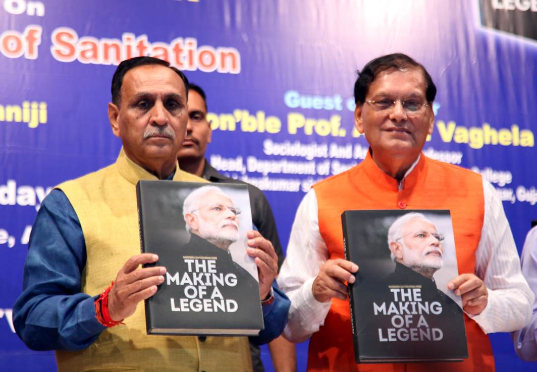 """PLEASE PERUSE: Gujarat Chief Minister Vijay R Rupani releases a coffee table book on Prime Minister Narendra Modi's """"The Making of Legend"""", authored by Dr Bindeshwar Pathak, founder of Sulabh International, at Thakhor Bhai Desai Hall in Ahmedabad, UNI"""