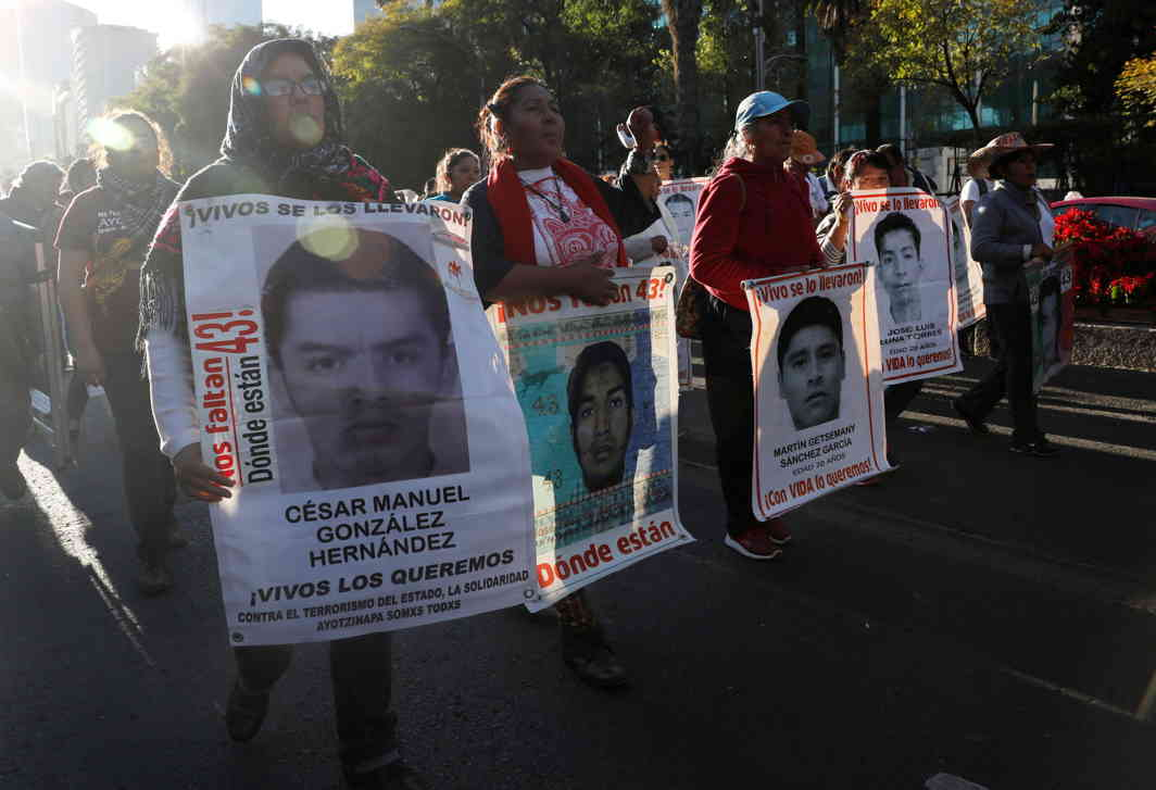 REMEMBER: Relatives hold posters with images of some of the 43 missing Ayotzinapa College Raul Isidro Burgos students during a march to mark the 38th month since their disappearance in the state of Guerrero, in Mexico City, Reuters/UNI
