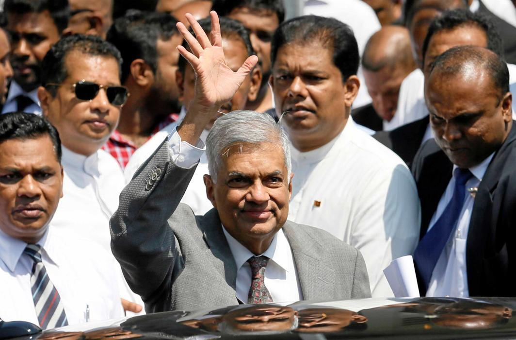 """LEADERLY ASSURANCE: Sri Lankan Prime Minister Ranil Wickremesinghe waves at the media as he leaves the """"presidential panel investigating into alleged irregularities in government bond sales"""" in Colombo, Reuters/UNI"""
