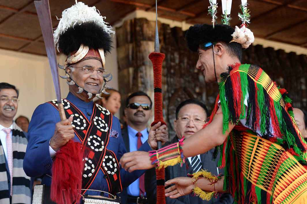 TRADITIONAL COLOURS: President Ram Nath Kovind being presented Naga attire during the inauguration of Hornbill Festival at Kisama in Nagaland, UNI