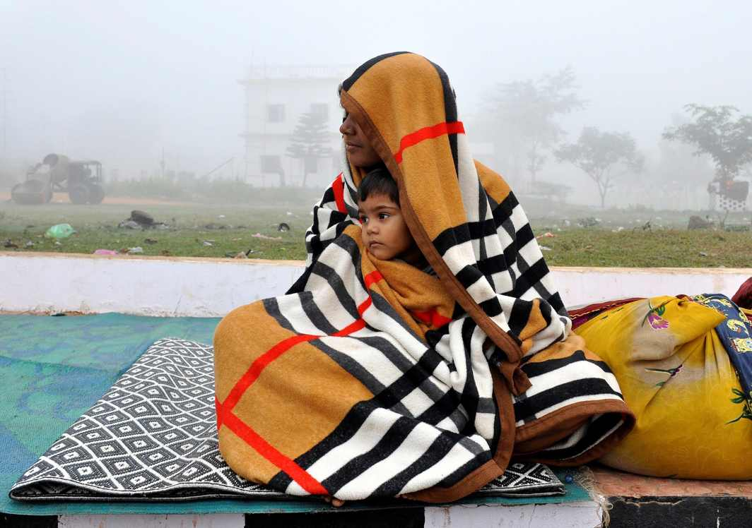 BODY LOVE: A woman and her son are wrapped in a blanket as they sit on a pavement on a cold winter morning on the outskirts of Agartala, Reuters/UNI